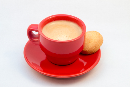 bica: Coffee served with biscuit in a generic red coffee cup on top of a saucer against a white background