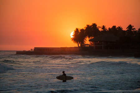 Surfer in the water during a sunset at Playa el Tunco, El Salvador Stock Photo