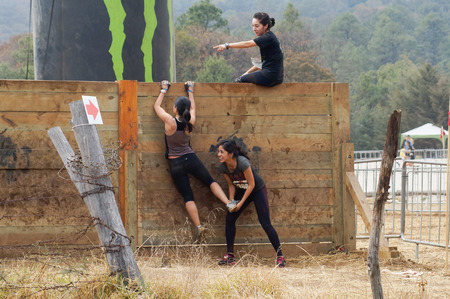 Young female athletes helping each other to climb a wooden wall obstacle during a extreme sports course. Editorial