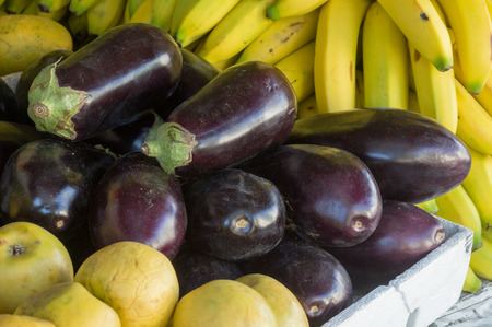 Eggplants or aubergines or eggfruit between bananas and guavas stacked in an organic market at Mexico. photo