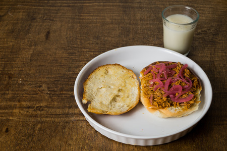Mexican Food Suckling Pig Pibil Sandwich served in a white dish and Horchata Water Glass on dark wooden table.  Torta de Cochinita Pibil  Tipical food of Yucatan  Mexico. Called Trancas Cooked with achiote.