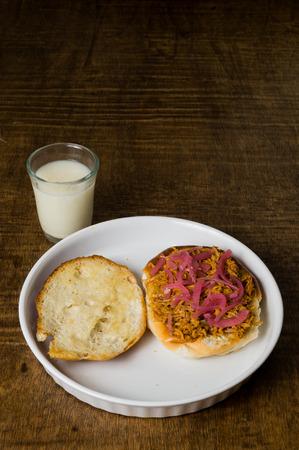 spanferkel: Mexican Food Spanferkel Pibil Sandwich serviert in einem wei�en Teller und Horchata Wasser-Glas auf dunklen Holztisch. Torta de Cochinita Pibil Typische Lebensmittel der Yucatan Mexico. Genannt Trancas mit achiote Hei� zubereitet.
