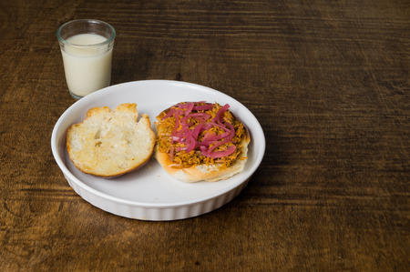 mexican food: Mexican Food Suckling Pig Pibil Sandwich served in a white dish and Horchata Water Glass on dark wooden table.  Torta de Cochinita Pibil  Tipical food of Yucatan  Mexico. Called Trancas Cooked with achiote.