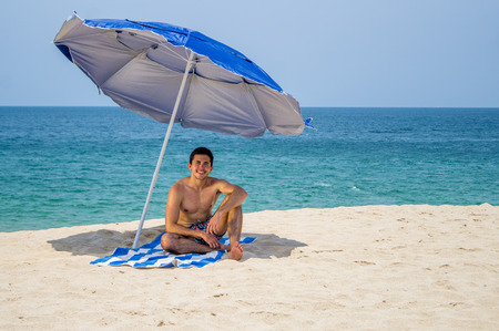 Athletic young male sitting on a towel under a blue and gray umbrella on the  beach with the ocean on the background