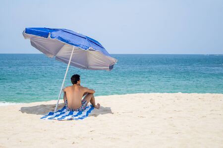 Athletic young male sitting backwards facing to the horizon on a towel under a blue and grey umbrella on the  beach with the ocean on the background.