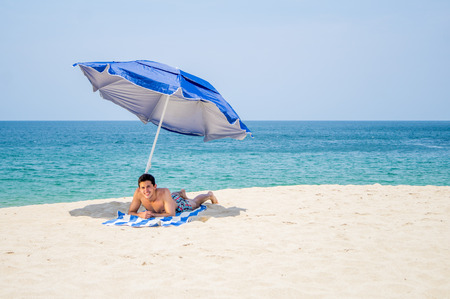 Athletic young male on laying down and facing to the camera on a towel under a blue and gray umbrella on the  beach with the ocean in the background Reklamní fotografie