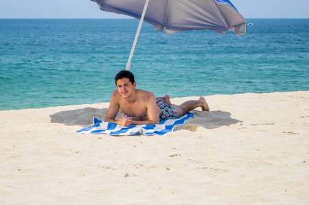 Athletic young male on laying down and facing to the camera on a towel under a blue and gray umbrella on the  beach with the ocean in the background Stok Fotoğraf