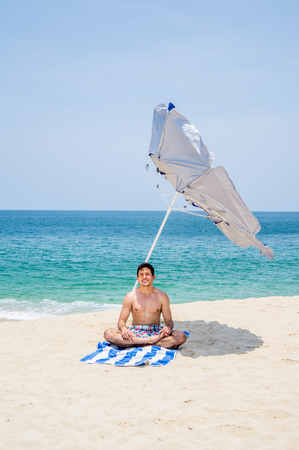 Athletic young male on yoga lotus position looking at the camera on a towel under a blue and gray umbrella on the  beach with the ocean on the background