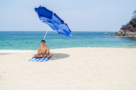 Athletic young male on yoga lotus position looking at the camera on a towel under a blue and gray umbrella on the  beach with the ocean on the background.