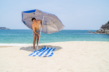 Athletic young man putting a blue and gray umbrella on the beach next to a towel with the ocean on the background.