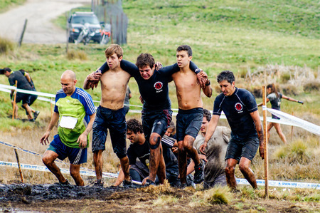 Spartan Race Sprint. Athletes crossing a muddy water pond.The Spartan Race is an extreme military style obstacles race where athletes run on hits of 300 participants, resembling the 300 spartans soldiers that fought under command of the legendary greek ge Editöryel