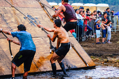 Spartan Race Sprint. Athletes crossing a muddy water pond.The Spartan Race is an extreme military style obstacles race where athletes run on hits of 300 participants, resembling the 300 spartans soldiers that fought under command of the legendary greek ge Redakční