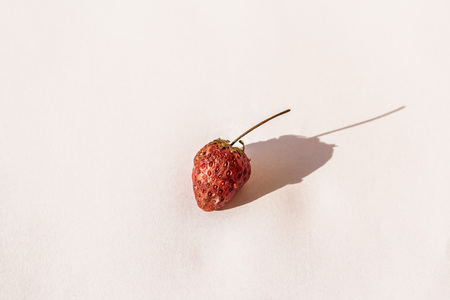 Rotten strawberries on white paper