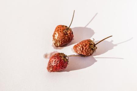 Rotten strawberries on white paper