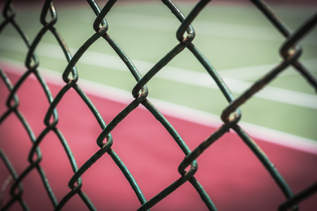 Close-up wire mesh steel with cort tennis background. Stock Photo