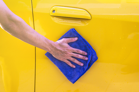 valeting: Man hand cleaning the car, using microfiber cloth for cleaning.