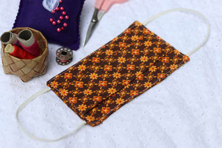 Sewing DIY cloth face masks in Thai pattern fabric on white blackground.  Thai people make own fabric masks because of a shortage of recommended supplies.