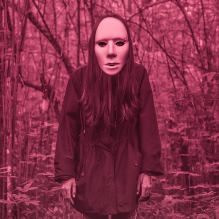 Halloween scary masked person in a scary Blood red forest landscape
