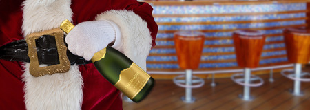 merry christmas Santa Claus holding a champagne bottle at the pub with bar and chairs background Stock Photo