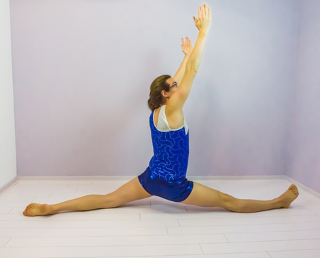 gymnastics flexibility exercise side split on the floor preformed by a young transgender girl wearing a shiny blue leotard