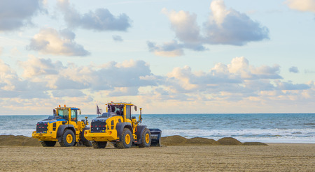 earthmoving equipment machines working at the beach for maintenance moving sand industrial agriculture Reklamní fotografie - 112920359