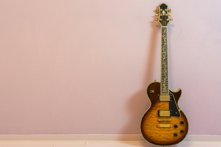 modern electric guitar with tree of life neck inlay, isolated on stone wall background Stockfoto
