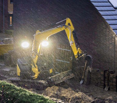 ground worker working at night in bad rainy weather, constructing a garden in the evening