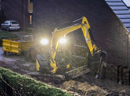 Travailleur au sol travaillant sur un jardin par mauvais temps pluvieux le soir