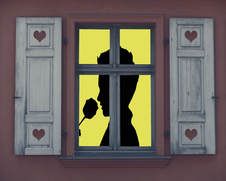 valentines day, a silhouette of a romantic person smelling a rose standing behind a lighted window