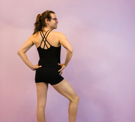 LGBT young girl posing in a black leotard with crossed back, standing in a elegant pose