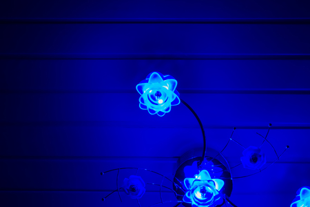 home interior background, a lighted modern lamp decorated with flowers hanging on the ceiling, shining blue light in the dark