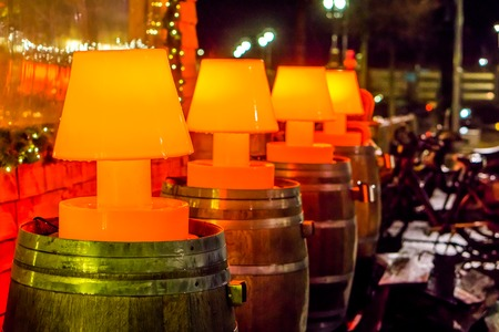 beautiful street decorations, line of lighted red lamps on wooden barrels, outdoor decoration Stock Photo