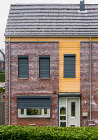modern dutch terrace house decorated with plants behind the windows, some windows closed down with roller shutters, home in a dutch small village