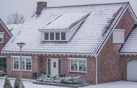 luxurious bungalow during a cold winter day, snowy weather, modern dutch architecture