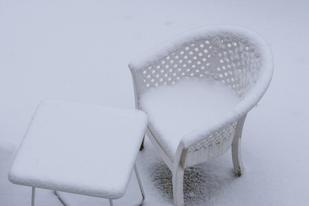 white table and lounge chair covered in a thick layer of snow during winter season, garden lounge set in the winter