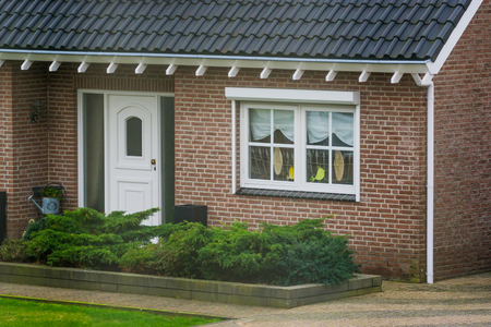front exterior of a luxurious dutch bungalow with a garden, front door with decorated window, home in a small village of the Netherlands