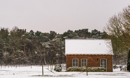 small farmers cottage in a winter landscape scenery, farm fields and house covered in snow, living near the forest