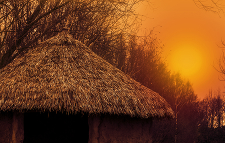 rooftop of a primitive home with a straw roof at sunset, nature scenery, beautiful landscape background