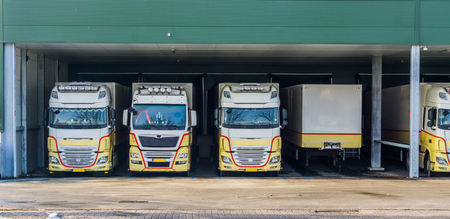 parked trucks at a docking station of a warehouse, logistics and transportation background
