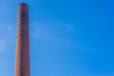 old historical stone chimney burner, old factory architecture, blue sky in the background Standard-Bild - 118889040