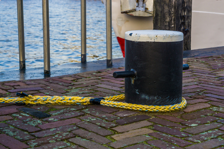 Docking pole with a rope to secure the boat, equipment at the harbor, water transportation background