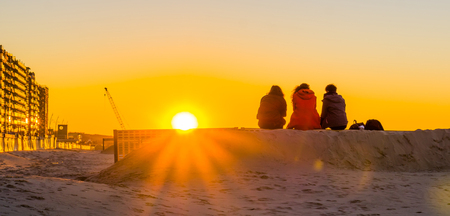 three teenagers sitting on a sand hill together, watching and enjoying the sunset at the beach, young people in nature 写真素材
