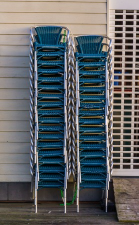 stacked chairs next to a closed rolling shutter, closing time in the catering industry Banque d'images