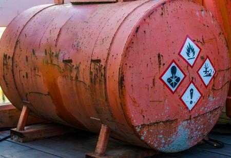ancien silo rouillé contenant des substances dangereuses, étiquettes d'avertissement sur le côté, stockage de liquides dangereux