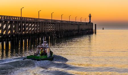 kleines Schiff im Hafen von Blankenberge, Belgien, der Steg mit Leuchtturm an der belgischen Küste