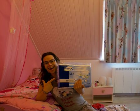 young person holding a package of Tena Ultima Confio Air, Medical Adult diapers, Popular brand for incontinence products Editorial