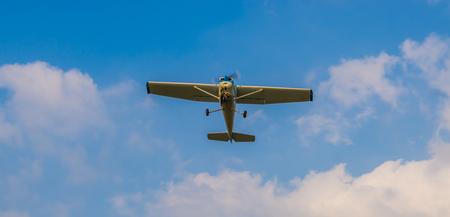 Avión de acrobacias volando en un cielo azul con nubes, transporte aéreo, pasatiempos y deportes Foto de archivo