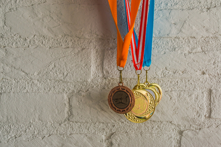rhythmic gymnastics medals hanging in front of a white brick wall, sport achievements