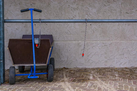 pulling trolley for luggage and kids, locked and leashed on a metal bar, outdoor transportation Imagens