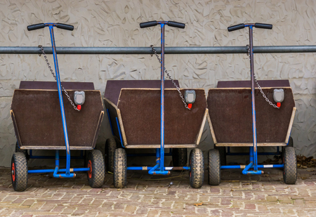 a row of pulling carts for baggage and children, locked and leashed on a metal bar, outdoor transportation